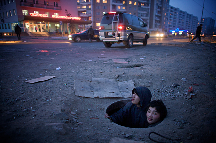 Munkhbat and Altangeret (both 15) have lived in this manhole together for over three years under the streets of Ulaanbaatar, the coldest capital city in the world. Spending time with them I witnessed what a tough, lonely and violent existence they have to endure in temperatures reaching -40c. They were forced into this situation by divorced and deceased parents but they still hope and strive for a better future. For me this image encapsulates the extremely difficult conditions these boys live in whilst life continues around them, oblivious and indifferent to their plight.""